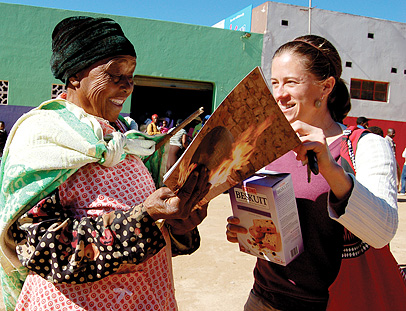 "Dr. Elizabeth Perrill, right, presents a copy of the ""Ukucwebezela:To Shine"" exhibition catalogue to Mamile Ngema, a retired potter."