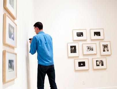 Joel Vanderkamp installs some of Andy Warhol's Polariods in the Weatherspoon Art Museum's McDowell Gallery. The exhibition, which includes close to 400 of the pop artist's photographs, will run through Sept. 19.