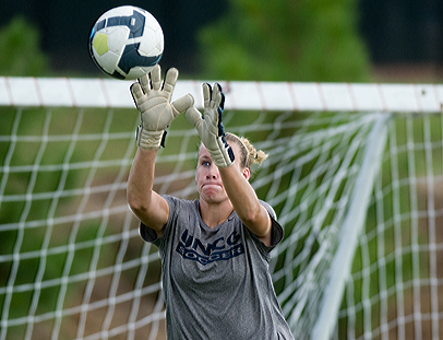 UNCG Goalkeeper Kelsey Kearney jumps up to block a shot to the goal during a practice.