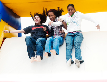 Britney, left, Vanessa, middle, and Jasmine slide down an inflatable slide during Spartan Village, part of the 2009 UNCG Homecoming festivities.
