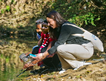 UNCG graduate student, Kristen Perez, works with students at the Welborn Academy in Highpoint, NC collect water samples from a local stream and test the quality of the water. She is working with the Welborn Academy through UNCG's STEM