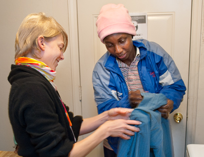 """Anya Russian, left, UNCG Access Americorps Caseworker, helps Honorine Ningatouloun, right, with her clothes. (Ningatouloun's daugher Gracia Fidelia Allah-Issem watches from the far left.) Ningatouloun took advantage of washers and dryers installed at Center for New North Carolinians. The washers have been installed to help draw immigrants to the """"center"""". Many of the immigrants started washing their clothes in bathtubs and sinks. They also typically dry their clothes on a drying ground. The washers have increased the sense of community and use of the CNNC's center."""