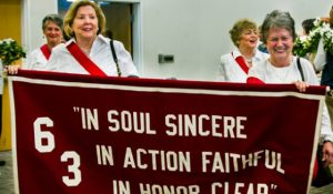 Image of class of '63 graduates carrying 1963 banner at reunion.