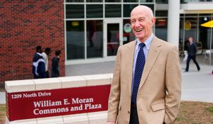 Dr. Moran poses in front of sign for the Moran Commons and Plaza named in his honor.