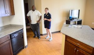 Photo of senior Tony Sanders and Chancellor Brady look over kitchen area