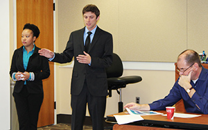 Photo of MBA students Ashley Ferrell and Will Kapakos and Bryan School Professor of Practice Richard Browne