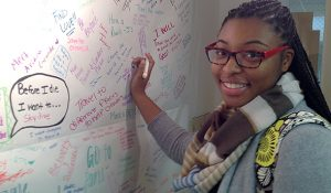 Photo of Jasmine Kendrick writing on the wall