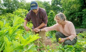 Photo of Dr. Susan Andreatta and Junior Antropolgy major, Seth Rumbley, observe vegetables in the gardens.