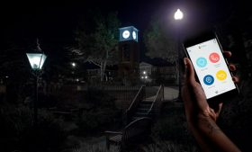 Night photo of UNCG campus with smartphone with Live Safe app