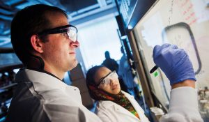 Photo of Dr. Mitchell Croatt works with research student in the chemistry lab