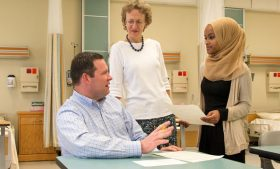 Photo of Zeinab Hassan interacting with Philip Simpson and Dr. Lynne Lewallen