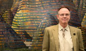 Photo of Will South, former curator of the Weatherspoon Art Museum, standing in front of Maud Gatewood artwork