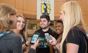Photo of students discussing the LiveSafe App in the Elliott University Center Rotunda