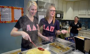 Photo of members of the Alpha Delta Pi sorority serving food at the Ronald McDonald House
