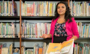 Portrait photo of Ruiz Mendez in front of book shelves
