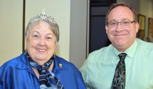 Group photo of Dr. Cherry Callahan with a tiara on standing with Tim Johnson