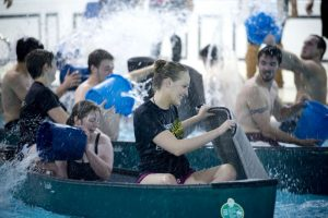Photo of UNCG students enjoy some friendly competition during the fall 2013 Battle Canoes event in Rosenthal Pool