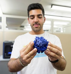 Navied Alamoudi holds a prototype made on one of the library's 3-D printers.
