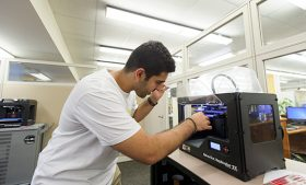 Navied Alamoudi sets up one of the library's 3-D printers.