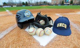 Staged photo of baseball cap, helmet, glove and baseballs at home plate