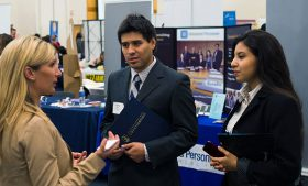 Photo of UNCG students talking with a representative at last year's career fair