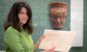 Donna Nash holds a map of excavation site in Peru and inset photo shows vessel from the dig.