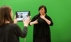 Photo of student with iPad recording session of student using sign language