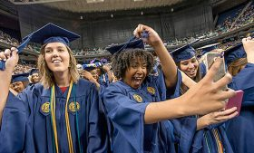 Photo of graduates taking selfies during Commencement to share on social media.