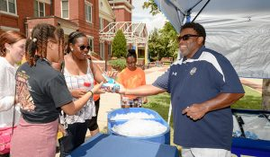 Photo of chancellor Gilliam helping students and families during move in.