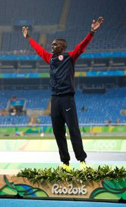Paul Chelimo celebrates on the podium before receiving his silver medal.