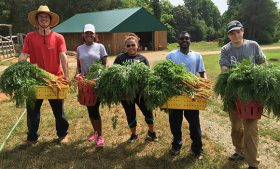 Photo of UNCG students with harvested food from Guilford College Farm