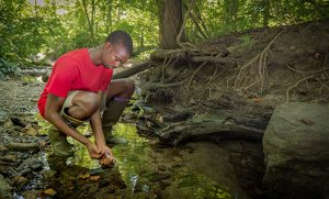 Photo of Austin Gray collecting water samples in stream.
