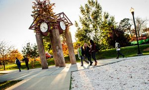 Campus picture of students walking around the clock tower