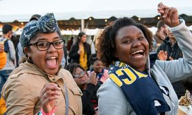 Photo of two students laughing at UNCG Homecoming