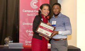 Joshua Leeper receives poses for a picture wiht the 2016 Community Impact Award plaque and North Carolina Campus Compact Executive Director Leslie Garvin.