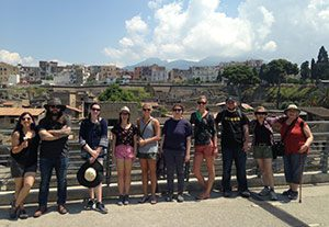 Group of students posing for a photo with archaeological site, city in the background.