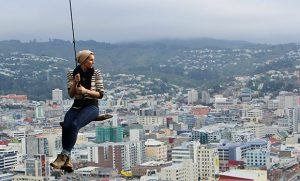 Photo of student on rope swing with city view in background.