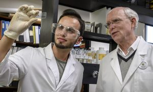 Photo of Faris Almubaslat and Dr. Bruce Kirchoff looking at a slide in the lab.