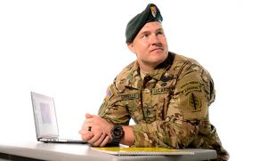 Photo of James Sorrells wearing military uniform and sitting at a desk
