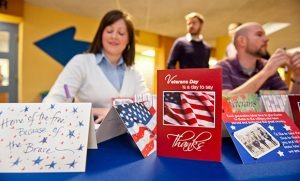 Staff and students sign cards for veterans