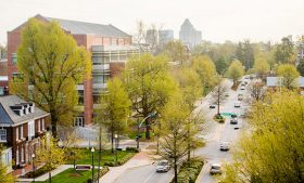 Campus shot of cars driving down Spring Garden Street with downtown skyline in the background