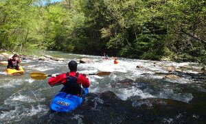A small group of students and staff paddle down Class II rapids.