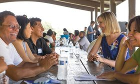Photo of Dr. Laura Gonzalez talking with families at picnic tables