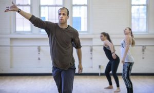 Photo of Talli Jackson teaching with two students dancing in the background