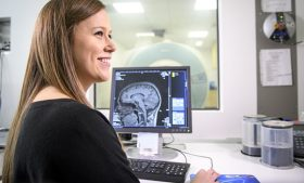 Photo of Margaret Scales with computer screen showing brain images in the background