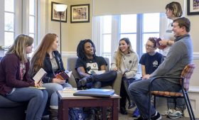 Group of students discussing a book with their Dr. Will Dodson