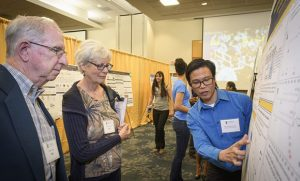 Photo of Rodell Barrientos pointing to poster presentation as attendees listen