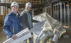 Photo of UNCG alumni Kayne Fisher and Chris Lester holding construction plans and wearing hard hats in unfinished restaurant space.