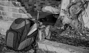 Black and white photo of backpack sitting on the ground