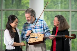 Qiaoyan Gao, David Holley and Nancy Walker talking, observing horsehead fiddle in Music Building